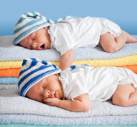 Doi bebei dorm pe tean de prosoape