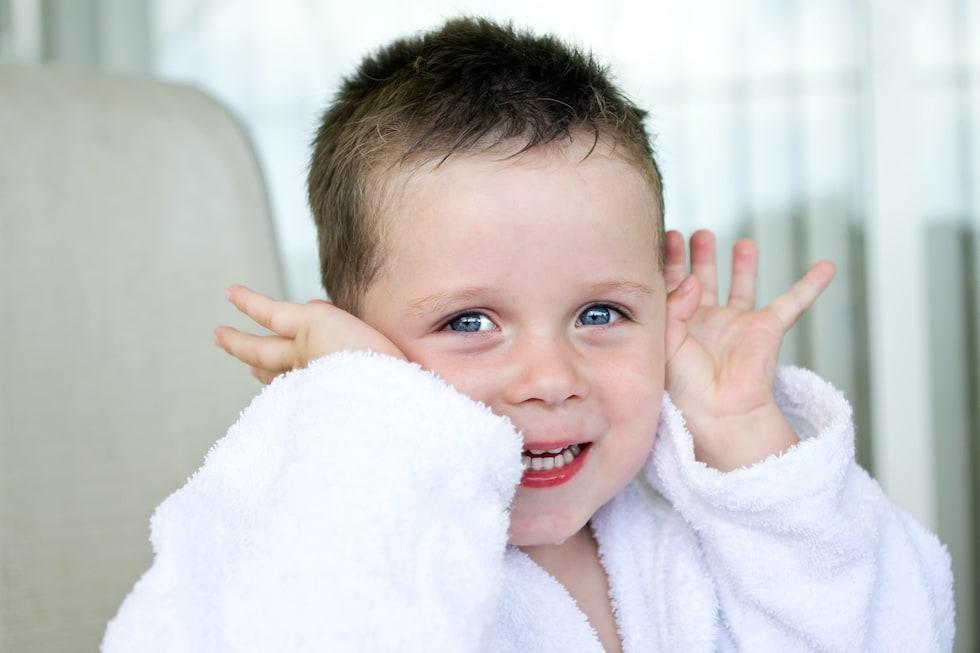 Baietel imbracat in halat de baie pentru copii