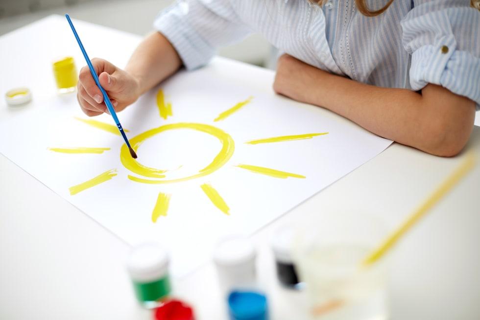 Copil deseneaza un soare cu acuarele