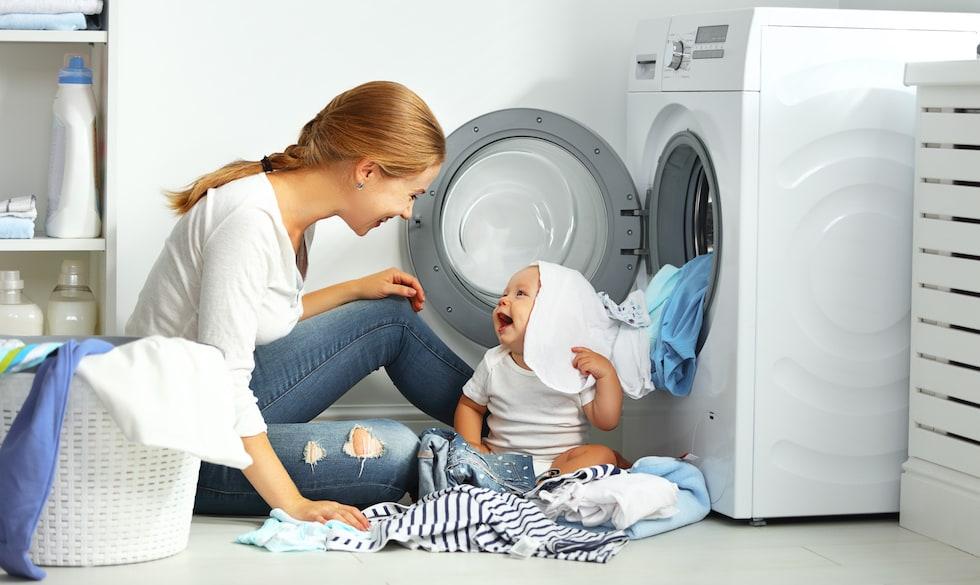 Mama impreuna cu bebelus pregatesc hainute pentru spalare