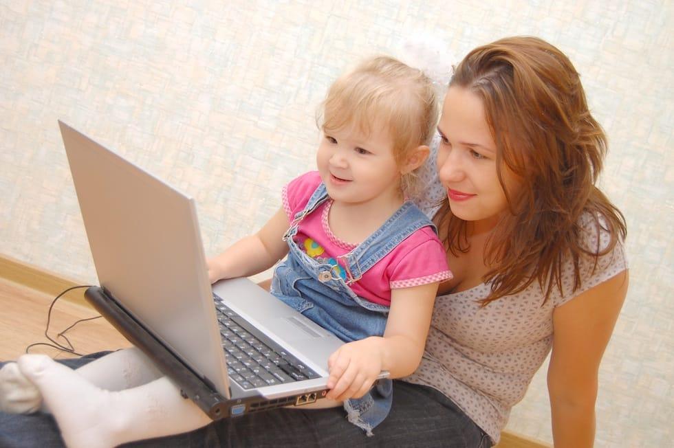 Fetita jucandu-se pe laptop