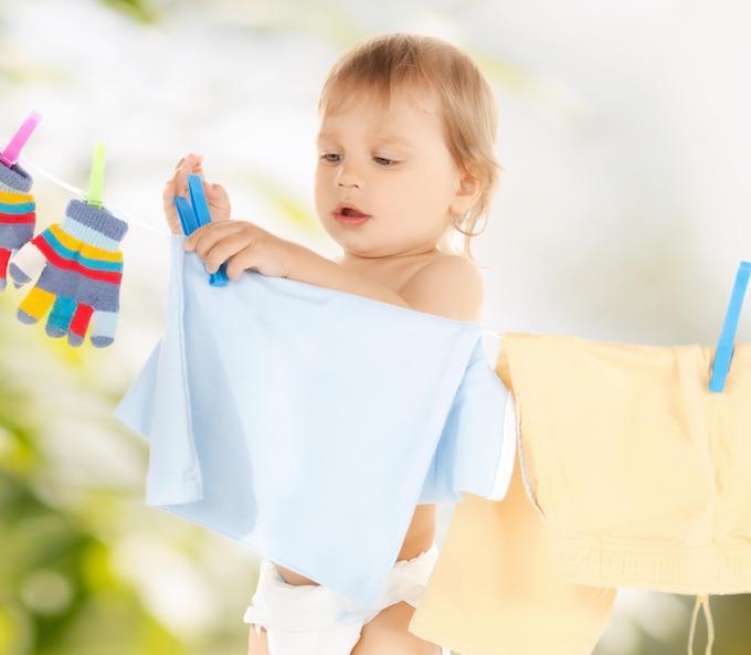 Copil pune hainute pe sarma