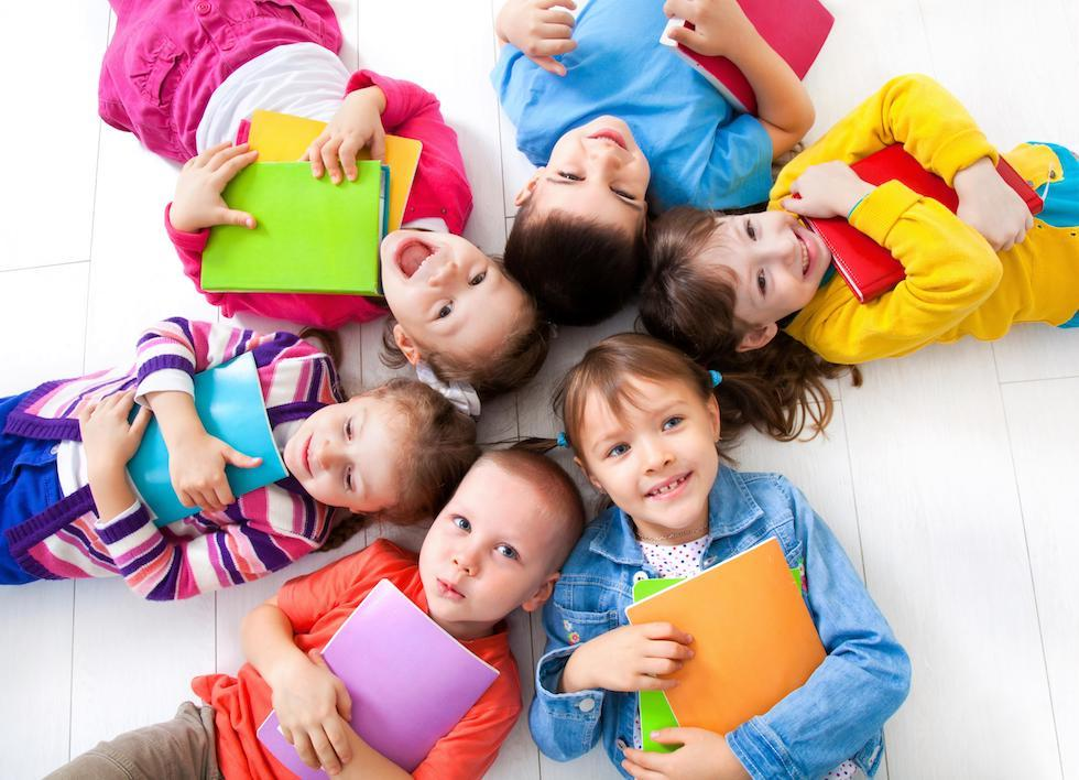 copii stand cu caietele in mana
