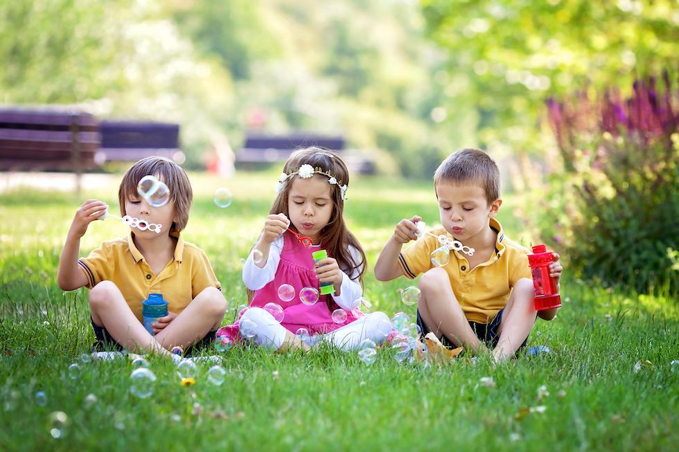 Copii care se joaca vara cu baloane de sapun