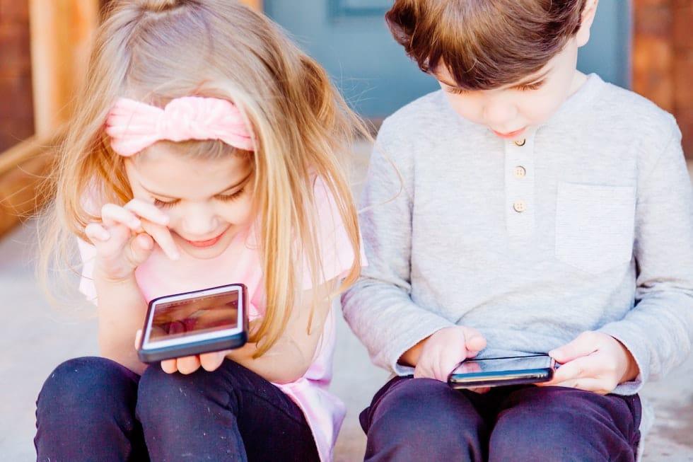Copii jucandu-se pe telefoane 1